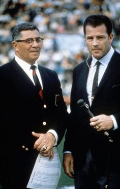 New York Giants head coach Vince Lombardi waits to be interviewed by New York Giants Hall of Fame running back Frank Gifford.