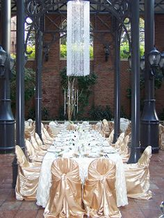 Captain-style head table for the bridal party with elegant gold chair covers, hanging crystals