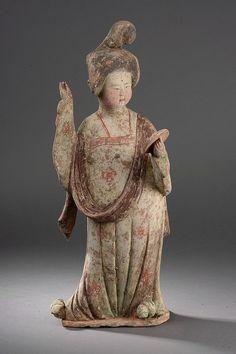 Princesse aux forme généreuses au faciès de lune coiffée d'un haut chignon élaborée et vêtue d'une longe robe retombant sur ses chaussures et maintenu par de fines bretelle orné d'une longue écharpe, tenant un miroir à la main. Terre cuite à engobe et polychromie. Chine. Dynastie Tang. 618 à 907. H 54cm