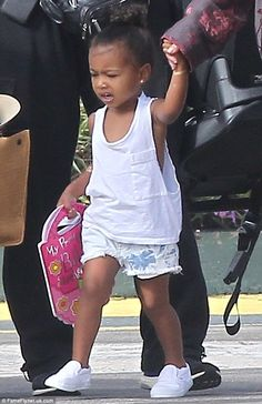 She has good reading material with her: North West carried a pink Bible-themed book with h...
