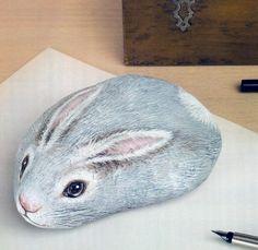 Pisapapeles.Piedra pintada como conejo.