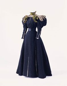 """1895, France Day dress by Gustave Beer Black bouclé silk; two-piece dress with """"gigot"""" sleeves; collar and yoke of layered silk satin and twill with cut work and bead embroidery; crescent-shaped velvet decoration on collar and shoulders; beige silk satin visible through all-over slit"""