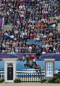 Tiana Coudray of the USA and her horse Ringwood Magister compete in the show-jumping phase of the equestrian eventing competition at the 2012 Summer Olympics, Tuesday, July 31, 2012, at Greenwich Park in London. (AP Photo/David Goldman)