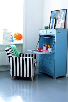 Ten niebieski sekretarzyk w stylu retro jest bardzo praktyczny, bo za uchylnym frontem-blatem można przy okazji ukryć biurowy rozgardiasz. Ponieważ formą przypomina komodę, postawiono go w salonie w parze z pasiastym fotelem. Wieczorami miejsce do pracy zmienia się w kącik wypoczynkowy.