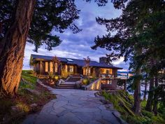 Beautiful vacation home in British Columbia sits on rock by water.  Great view through large windows.  Open concept and tall ceilings - connected with nature.