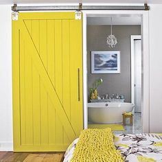 A standard swinging door can take a lot of floor space in your bath, but a sliding door is convenient and compact. A modern barn door slides along a track to close off this bath. The bright saffron color ties in with the saffron-and-gray bedding and updates the look. | SouthernLiving.com