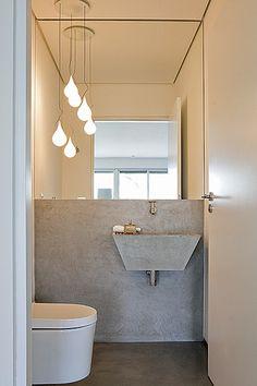 O piso do lavabo é de tecnocimento e a parede, revestida de limestone – mesma pedra da pia, desenhada pelos arquitetos da SAO Arquitetura. Os pendentes deixam o ambiente ainda mais moderno
