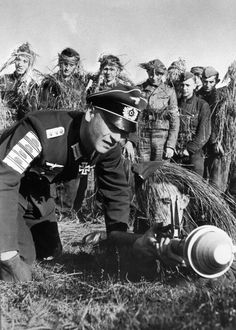 "Cpt Peter Kisgen, ace tank destroyer, instructs young recruits in the handling of the anti-tank ""Panzerfaust"" German bazooka. Note the tank destruction badges on his sleeve."