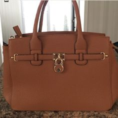 """Robert Matthew Hailey Tote Robert Matthew Hailey Tote Color: Saddle             Faux Leather, Top Zip Compartment, Polyester Lining, Handle Drop 5"""", Metal Alloy Hardware.     Dimensions: 14""""W x 9""""H x 6""""D.                             Four Pockets: exterior zip pocket, interior zip pocket, two open pockets. Bags"""