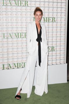 Erin Wasson wears a black tie-front top, white suit, and furry heels