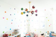 Sputnik style chandelier with rainbow colored shades and mid century modern design.  Great for kids bedrooms and more.