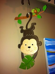 Nursery DIY jungle/ safari theme- felt monkey stickers from dollar store with buttons added for decoration.