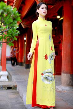 Áo dài truyền thống màu vàng vẽ hoa Sen đỏ giúp làn da của Quý Cô được sáng hơn trắng hơn và thêm phần tự tin khi dạo bước trên những góc phố.