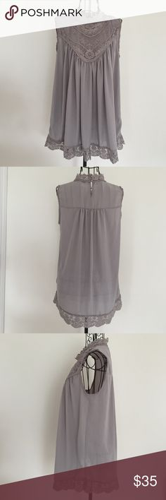 """Gray sleeveless shirt. NWOT Gray sleeveless shirt with lace detail at chest, arms and around the bottom.  Two buttons in back. Bust 21"""". Length 27"""" A dip of Darling Tops"""