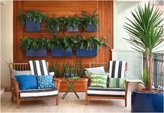Uma parede inteira de plantas e um jardim que exija pouca manutenção. A solução criada pela paisagista Claudia Diamant foi um grande e charmoso painel feito com diferentes larguras de madeira cumaru, que acomoda uma jardineira e sete cachepôs de aço, pintados de azul
