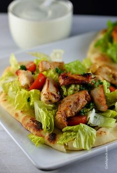 Chicken Souvlaki makes a delicious, quick recipe for lunch or supper. Chicken, seasoned to perfect, piled on top of grilled Naan bread with romaine and tomatoes and drizzled with tzatziki.