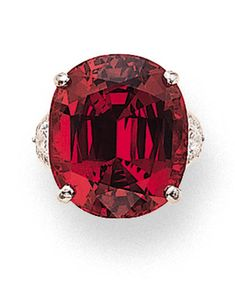 A SPINEL AND DIAMOND RING   Set with a cushion-shaped red spinel weighing 22.97 carats with pear-shaped diamond shoulders and circular-cut diamond mount to the polished and brushed white gold hoop  With certificate 8804026-1 dated 15 April 1988 from the Gübelin Gemmological Laboratory stating that the stone is a natural spinel