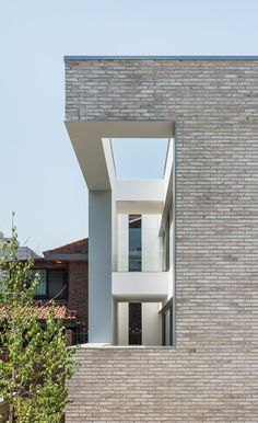 Cutaways in the brick facade of this family home by Seoul studio OBBA provide views over a small walled garden