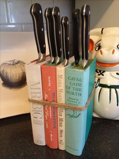 DIY knife block - I just glued together the covers of some interesting books i found at the thrift store and secured them with twine. the tight pages of the books hold the knives in place. plus at 4 dollars total cost i can afford to do this again in a few years when the books start to shred.