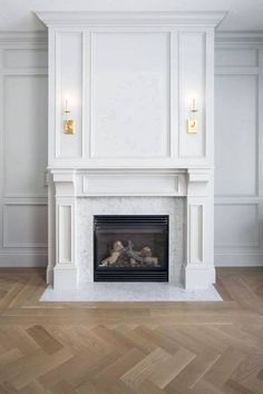 Traditional sitting room + herringbone flooring + white fireplace + wall paneling + art above fireplace + sconces on mantle + traditional fireplace design Fireplace Trim, Marble Fireplace Surround, Marble Fireplaces, Fireplace Wall, Living Room With Fireplace, Fireplace Surrounds, Fireplace Design, Home Living Room, White Fireplace Mantels