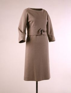 """Gray double-knit wool dress and overblouse, by Hubert de Givenchy, French, ca. 1959. The overblouse, made popular in America by Jacqueline Kennedy, has a neckline that was cut to stand up and away from the shoulder blades and a deep bias band at the hem that impedes its fall. The layering without bulk is achieved by """"shrugging"""" the overblouse over the dress's silk top. Worn by Mrs. John F. Kennedy during the 1960 presidential campaign."""