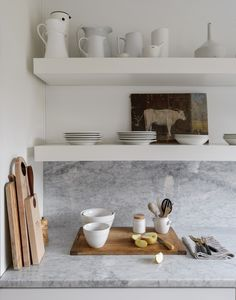 Floating open shelves display our collection of white stoneware dishes; most of the pieces are from Sweden and England. The backsplash and countertops are Carrara marble. #remodelista