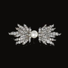 Natural pearl and diamond brooch, late 19th century   In the form of the middle section of the Neck Badge of the Austrian Order of the Golden Fleece, set with a button-shaped natural pearl measuring from approximately 6.5 to 11.3mm and rose, circular- and single-cut diamonds.