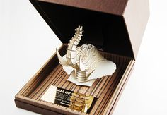A custom safari themed invitation for a private party. A 3D cardboard elephant head was mounted to a Zebra wood base with an etched gold metal invitation plaque. Best Invitation Winner of the National 2013 BizBash Event Style Award
