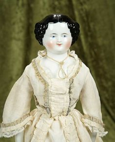 "20"" German porcelain lady with sculpted black hair and rare smiling expression~~~Porcelain shoulder head with black sculpted curls in scalloped arrangement around the face, painted blue eyes and facial features, closed mouth with upturned lip corners in smiling expression, old muslin body, porcelain lower limbs, painted black boots, nice antique gown.  Germany, circa 1875."