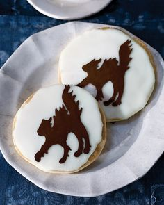 "Inspired by an Edgar Allan Poe story in which a demonic cat is ""graven in bas-relief upon the white surface"" of a wall, these cakey black-and-white cookies feature the chocolate silhouette of a fur-raised feline set against a full moon of glossy icing."
