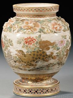 Japanese Satsuma vase of ovoid shape with enamel and gold decoration of lions in a landscape with flowewrs, water and rocks, high relief gilded and enameledpeonies form a band at the shoulder, with brocadedesign bands at neck and base, on pierced stylized floral foot, Japan, circa 1801-1900