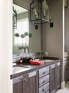 Black-iron fixtures and cabinets crafted from reclaimed barn wood forge a connection to country carriage houses and farm homes of yesteryear. The dual-sink farmhouse bathroom vanity sports vintage-style bin pulls and latches and a modern concrete countertop stained to match the cabinet's deepest tones./