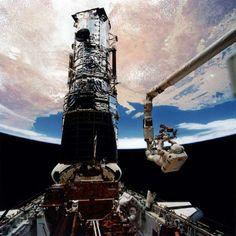 El astronauta Sory Musgrave, anclado en el brazo del Sistema Manipulador Remoto, se prepara para instalar cubiertas protectoras en los magnetómetros del Telescopio Espacial Hubble. El astronauta Jeffrey Hoffman (parte inferior del cuadro) le ayuda, 9 de diciembre de 1993. © REUTERS/NASA/Handout