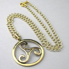 """Large size gold filled pewter triskele triple spiral pendant comes with a long sturdy cable chain that fastens with a bright gold plated lobster clasp.  The triskele has a smooth, opened, curved shape. The opposite side has a textured surface. See photo 9. Necklace is handmade by The Singing Beader.   See all 10 photos showing details.   A lovely piece for one who likes symbolic or Celtic jewelry. See inspiration below.  Chain length: 24"""" (60.96 cm) Triskele: 44 mm (approximately 2 3/4"""")..."""