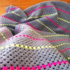 A simple crochet granny stripe blanket made from grey and neon yellow and pink acrylic yarn
