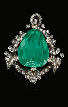An emerald and diamond pendant, late 19th century. Set at the centre with a pear-shaped emerald, within a foliate border highlighted with rose diamonds.