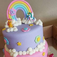 My Little Pony Cake Pink and purple My Little Pony Cake with rainbow cake topper and fluffy clouds with little ponies scattered on the cake...