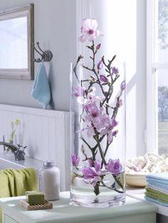 Die Zartheit der pastelligen Magnolien kommt prima in der schlichten Glasvase zur Geltung, die gut ins Badzimmer passt.