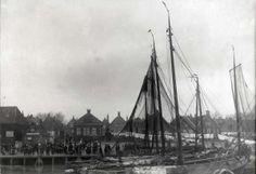 Steden en dorpen. De boot Max Havelaar vertrekt. Aan de wal staan Urkers te kijken. Verderop lange rijen wasgoed aan de lijnen voor de huisjes van Urk. 1915 #Urk