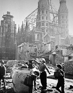 Vor dem völlig ausgebrannten Stephansdom spielen Kinder in den Trümmern der zerstörten Häuser und suchen nach verwertbaren Gegenständen.