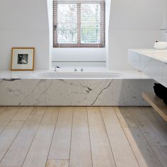 Love the wood against the marbled bathtub. Chic!