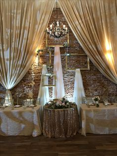 Champagne drapes   head table   sweetheart center   rose gold sequin   white uplighting  chandeliers   brick backdrop  gold frames with hanging drapes   monogram light   wedding held at The Century Modesto, CA