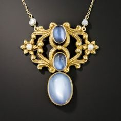 A syzygy (astronomy: a collinear configuration of three celestial bodies), in this case a trio of luminous blue flash moonstones, glisten and glow in this dreamy Art Nouveau lavallière necklace artfully and sinuously rendered in 14K yellow gold and dotted with 4 tiny pearls - circa 1900. 1 1/2 inches, 19 inches long.