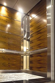 This Elevator Interior utilized both durable and natural materials to provide a strong architectural unity between the structure of the building and the interior design. Centered on all non-access walls are four horizontal wood core panels faced with  Rosewood Veneer and framed with 7mm stainless steel trims. Each corner has two 6mm vertical clear safety mirrors aligning with panels complete with stainless steel trims.