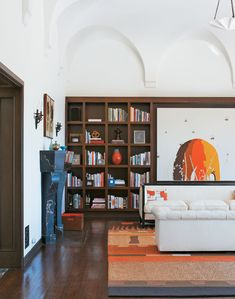 The living room of Shearmur's home is stately and minimal. The bookshelves contain an amazing array of art books as well as smaller collected pieces.