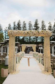 An arbor adorned with creamy roses and garlands of ivory orchids marked the entrance to the outdoor ceremony. The petal-lined aisle led to a large chuppah situated in front of a romantic waterfall. Photography: John Solano Photography Read More: http://www.insideweddings.com/weddings/luxurious-traditional-wedding-at-four-seasons-westlake-village/374/