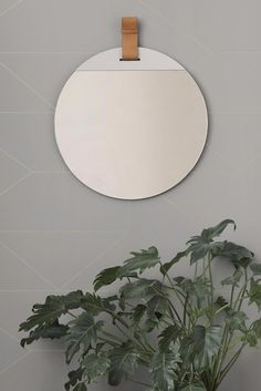 Enter Mirror By Soren Rose Studio for Ferm Living Includes a round mirrored surface on a powder coated metal backing, which is accented by a harness leather loop. Hidden within the loop is a metal grommet for easy wall hanging.