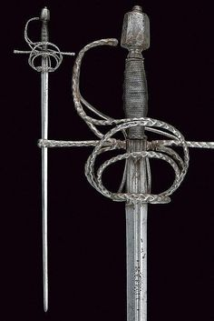 """A composite rapier. Circa 1600. Spain. Straight, double-edged blade ribbed at the centre, the first part grooved at the centre, featuring the signature """"VALENCIA MEFECIT"""", grooved ricasso with outlined margins; iron hilt, quillons, lower-rings, parry rings and guard all chiselled with waves, replaced but coeval pommel; grip with iron wire binding and moor's heads."""