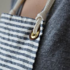 Stay tidy in the kitchen, garden or workshop. Our unisex Apron No. 2 offers ample coverage and more length.  • 5.3 oz. flax linen (Flax and Brown Linen)/ organic cotton and hemp (Chambray and Indigo Stripe) • Hand hammered brass grommets. • Washers made from repurposed leather. • Two patch pockets. • 29 w x 30h. • Machine wash. • Handcrafted in upstate New York.