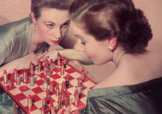 1955  Two models are playing an unusual game of chess, with lipstick instead of chess pieces.